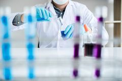 stock image of  biochemistry laboratory research, scientist or medical in lab coat holding test tube with reagent with drop of color liquid over