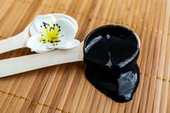 stock image of  black substance in wooden jar on a wooden background.