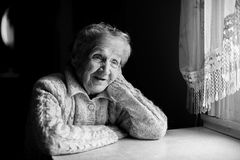 stock image of  black and white contrast portrait of an elderly happy woman.