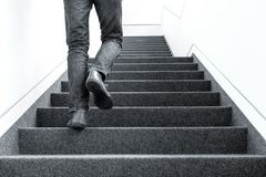 stock image of  low angle picture of man walking upstairs on indoors