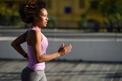 stock image of  black woman, afro hairstyle, running outdoors in urban road.