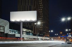 stock image of  blank illuminated billboard near well-lit road at night time. 3d rendering