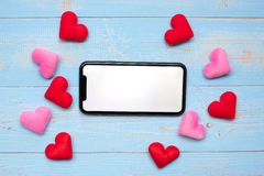 stock image of  blank touchscreen display of black smart phone with red and pink hearts shape decoration on blue wooden table background. love,