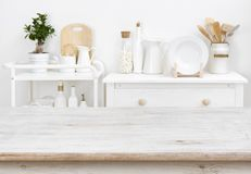 stock image of  bleached tabletop with copyspace over blurred kitchen furniture with tools