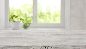 stock image of  bleached vintage wooden tabletop with blurred window for product display