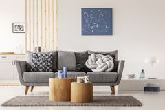 stock image of  blue abstract painting on white wall of contemporary living room interior with grey settee with pillows