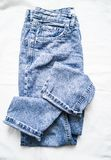 stock image of  blue faded mom jeans on a light background, top view. fashion clothing