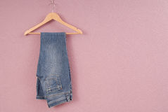 stock image of  a blue jeans are on hanger.