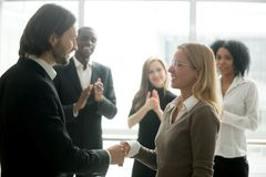 stock image of  boss handshaking employee congratulating with promotion while di