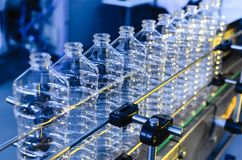 stock image of  bottle. industrial production of plastic pet bottles. factory line for manufacturing polyethylene bottles. transparent food packag