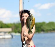 stock image of  boy catching a fish in michigan lake during summer, fishing activity with family. fun child.