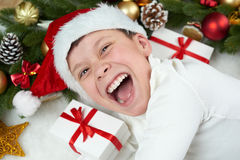 stock image of  boy child having fun with christmas decoration, face expression and happy emotions, dressed in santa hat, lie on white fur backgro
