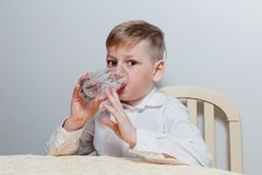 stock image of  a boy drinks water from a glass cup