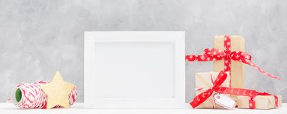 stock image of  bright christmas mock up with photo frame: festive gift boxes, wrapping thread and gold star. new year concept