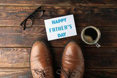 stock image of  brown leather shoes, inscription happy fathers day, cup of coffee and glasses on wooden background, space for text