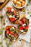 stock image of  bruschetta with grilled eggplant, cherry tomatoes, feta cheese, capers and fresh aromatic herbs on a wooden table. delicious medit