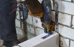 stock image of  builder screwing joining clamp in aerated concrete block with electric drill