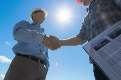 stock image of  builders handshake, architect and contractor agreement during meeting discussing blueprint buiding plan on construction
