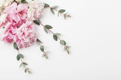 stock image of  bunch of beautiful flowers and eucalyptus leaves on white table top view. flat lay style.