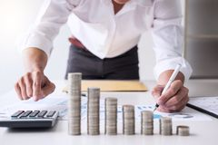 stock image of  business accountant or banker, businessman calculate and analysis with stock financial indices and putting growth stacking coin