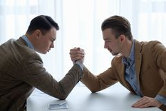 stock image of  business competition arm wrestling focused men hands