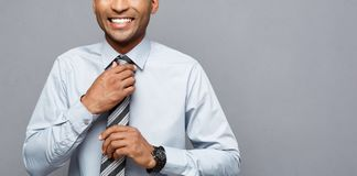 stock image of  business concept - happy confident professional african american businessman posing over grey background.