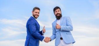 stock image of  business partner confirming deal transaction. men formal suits shaking hands blue sky background. entrepreneurs shaking