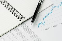 stock image of  business perfomance review, budget, economics or investment concept, pen on note book with graph and chart, price numbers report