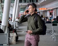 stock image of  businessman in a hat standing at the airport,talking by cellphone .
