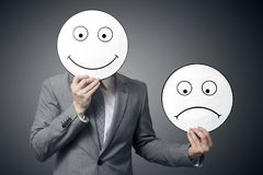 stock image of  businessman holding smile and sad mask. conceptual image of a man changing his mood from bad to good