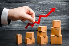 stock image of  a businessman`s hand holds a red arrow up above cardboard boxes folded incrementally. sales growth and increase in exports