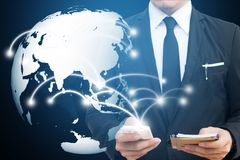 stock image of  businessman touching global network and mobile phone. communication and social media concepts