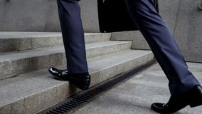 stock image of  businessman walking up stairs, success in career concept, promotion, closeup