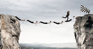 stock image of  businessmen support bridge to get to the flag. achievement business goal concept