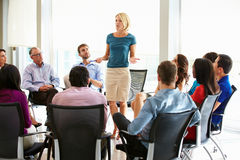 stock image of  businesswoman addressing multi-cultural office staff meeting