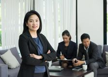 stock image of  businesswoman female leader standing and cross arm with team in