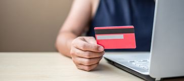 stock image of  businesswoman holding credit card for online shopping while making orders via the internet. business, technology, ecommerce and