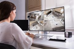 stock image of  businesswoman monitoring cctv footage on computer