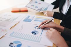 stock image of  businesswoman pointing pen on business document at meeting room.discussion and analysis data charts and graphs showing the results