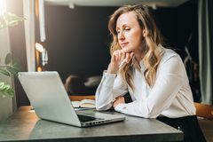 stock image of  businesswoman in white shirt is sitting in office at table in front of computer and pensively looks at screen of laptop
