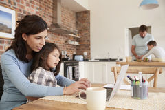 stock image of  busy family home with mother working as father prepares meal