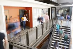 stock image of  busy high school corridor during recess with blurred students and staff