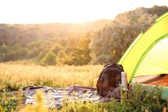 stock image of  camping gear and tourist tent in wilderness