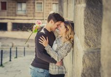 stock image of  candid portrait of beautiful european couple with rose in love kissing on street alley celebrating valentines day