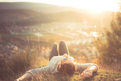 stock image of  carefree happy woman lying on green grass meadow on top of mountain edge cliff enjoying sun on her face. enjoying nature sunset