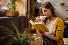 stock image of  casual woman reading a book while drinking