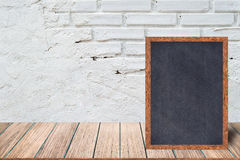 stock image of  chalkboard wood frame, blackboard sign menu on wooden table and with brick background.