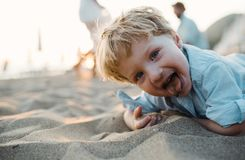 stock image of  a small toddler boy standing on beach on summer holiday, having fun.