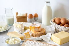 stock image of  cheese, milk, dairy products and eggs on rustic white wood background.