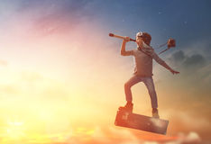 stock image of  child flying on a suitcase